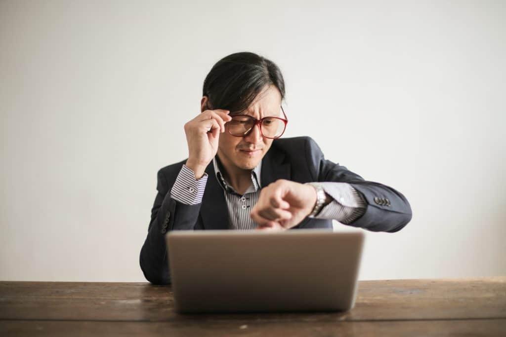 Man at computer looking at watch